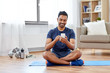 sport, technology and healthy lifestyle concept - smiling indian man with smartphone sitting on exercise mat at home