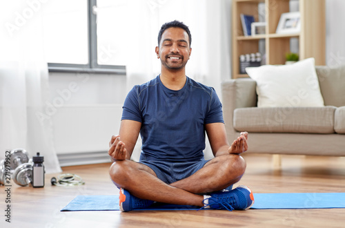 Obraz fitness, meditation and healthy lifestyle concept - indian man meditating in lotus pose on exercise mat at home - fototapety do salonu