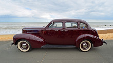 Classic Dark Red Studebaker  Motor Car Parked  On Seafront Promenade Beach And Sea In Background.