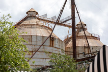 Two Rusty Round Silos On A Clo...