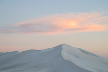 Scenic View Of Sand Dune Against Sky During Sunset