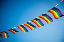 Gay Pride Rainbow Flag Bunting Fluttering Against Blue Sky Copy Space