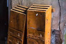 Two Light Brown Rusted Mailboxes With Peeling Paint Hanging On A Wall With Cracks In One Of The Courtyards Of The Uzupis Republic In Vilnius, Lithuania. Old Abandoned Mail Boxes For Post.