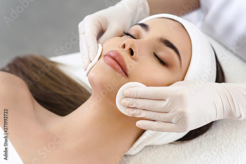 close-up-of-hands-of-skillful-beautician-cleaning-and-touching-female-face-with-cotton-pad-or-sponge-the-woman-is-lying-and-relaxing-her-eyes-are-closed-with-pleasure