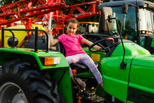 Cute Little Girl Playing By Driving A Old Tractor In Farm