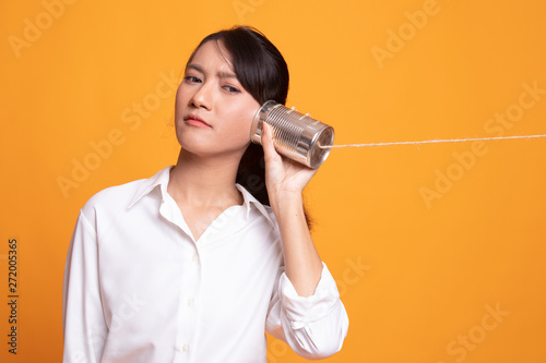 Photo  Young Asian woman with tin can phone.