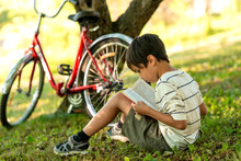 The Boy Sits On The Grass In The Garden And Thinks About The Book Read.  A Red Bicycle Stands By A Tree, A Book Is Lying On The Grass