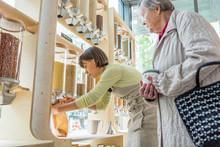 Young Female Shopkeeper Helping Elderly Lady In Zero Waste Store.