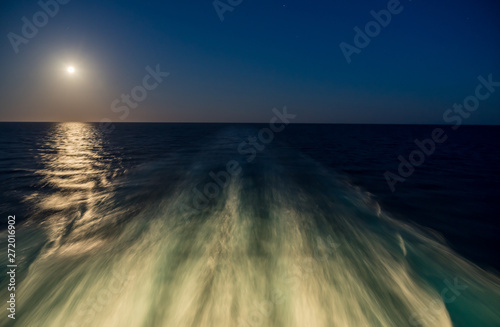 Moon rising over wake and waves of cruise ship at sea with concept of leaving or Wallpaper Mural