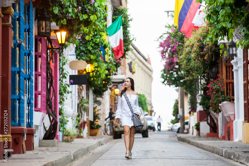 Fényképezés  Beautiful woman on white dress walking alone at the colorful streets of the colo