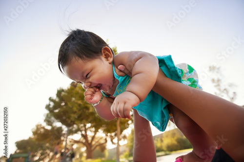 Baby girl being lifted up by mother into the sky, baby looks excited and nervous Wallpaper Mural