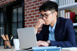 Young asian businessman concentrate on working with laptop computer at office, business people and office lifestyle concept
