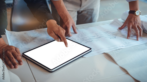 Fototapeta Team of construction engineers discussing paper blueprint and mockup tablet white screen for graphic montage. Architect using technology concept obraz na płótnie