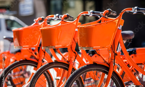 Fotografie, Obraz  Orange bikes for public hire stand in row at the station waiting for those who w