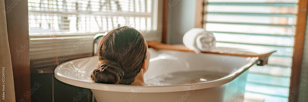 Fototapeta Luxury bath woman relaxing in hot bathtub in hotel resort suite room enjoying pampering spa moment lifestyle banner panorama.