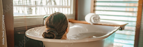 Foto Luxury bath woman relaxing in hot bathtub in hotel resort suite room enjoying pampering spa moment lifestyle banner panorama
