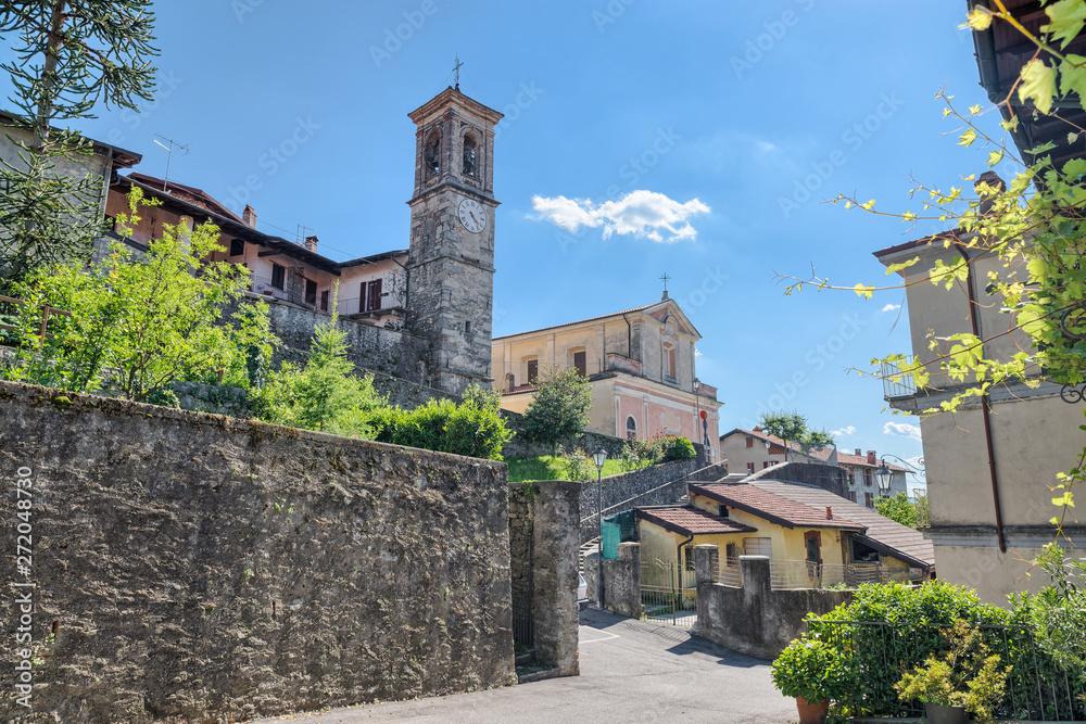 Fototapeta Historic center of Azzio, village in north Italy on the edge of the Campo dei Fiori regional park, province of Varese. Parish Beata Vergine Annunziata di Azzio of 1400, enlarged in 1749, street Cavour