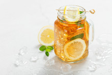 Iced Tea With Lemon Slices And Mint On Light Gray Stone Background.