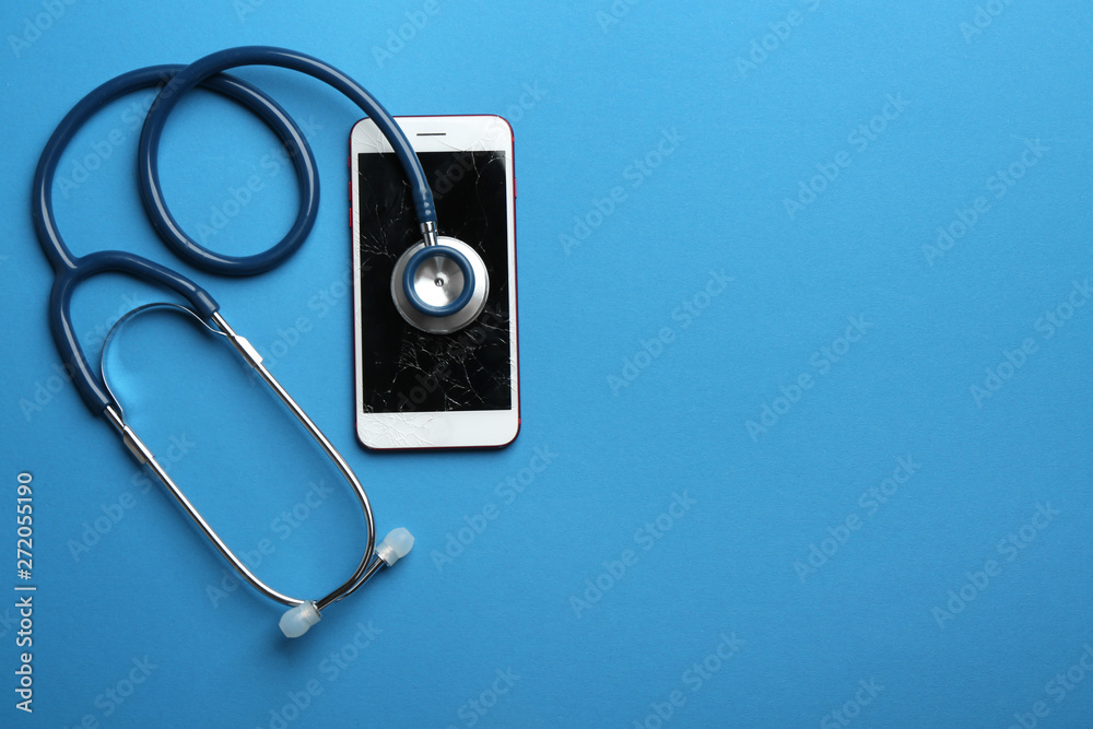 Fototapeta Modern smartphone with broken display, stethoscope and space for text on color background, flat lay. Device repair service