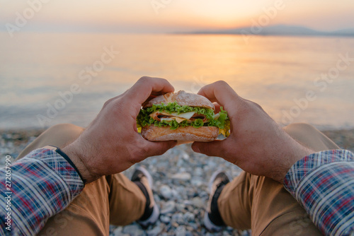 Poster de jardin Cote Young man resting with burger by the sea, pov.