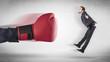Leinwandbild Motiv Big red boxing gloves hitting little businessman concept