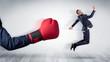Leinwandbild Motiv Big red boxing glove knocks out little businessman concept