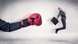 Leinwandbild Motiv Huge Boxing Gloves punches innocent businessman concept