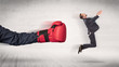 Leinwandbild Motiv Arm with red boxing gloves hits office worker concept
