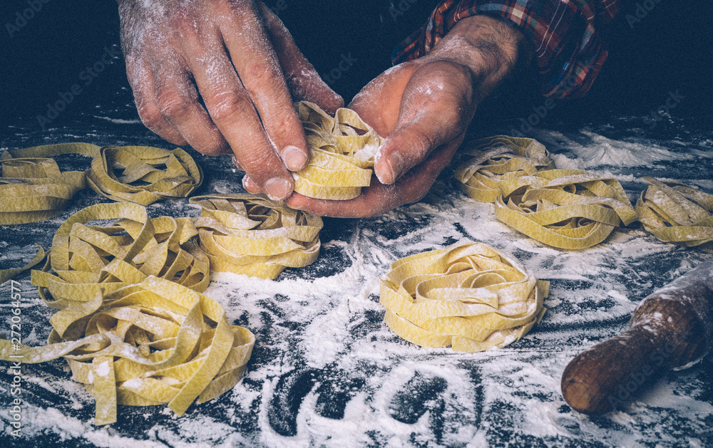 Fototapety, obrazy: Homemade uncooked pasta on black background. Making fresh italian fettuccine.