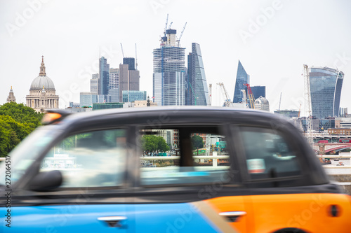 London cityscape with a black cab in motion at the foreground Wallpaper Mural