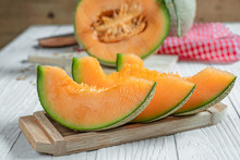 Fresh Of Whole And Sliced Orange Melon Or Cantaloupe On Tray Board And Background Wooden Table. Favorite Fruit In Summer Concept.