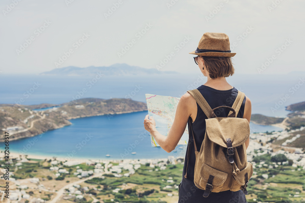 Fototapeta Woman traveler with backpack holding map. Travel, tourism, summer holidays, active lifestyle concept. Hipster tourist girl looking for hiking route with sea and villages at background
