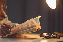 Woman Reading Book At Evening At Home Close Up