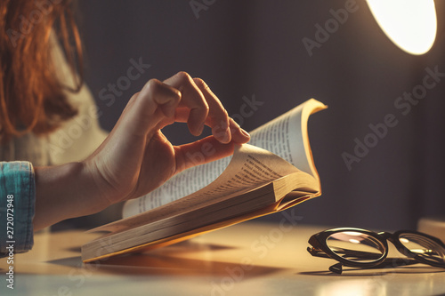 Fototapeta Woman reading book at evening at home close up obraz