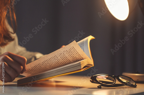 Woman reading book at evening at home close up Wallpaper Mural