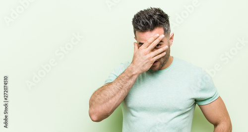 Valokuva  Young handsome man against a green background blink at the camera through fingers, embarrassed covering face