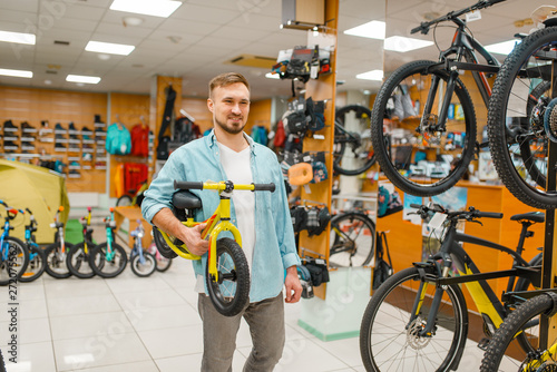 fototapeta na drzwi i meble Young father with children's bicycle, shopping