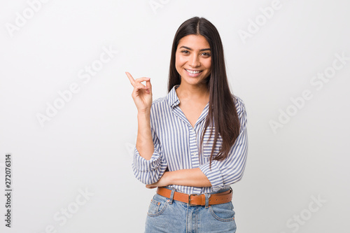 Cuadros en Lienzo  Young pretty arab woman smiling cheerfully pointing with forefinger away