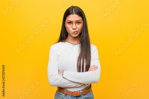 Fotografie, Obraz  Young pretty arab woman against a yellow background frowning face in displeasure, keeps arms folded