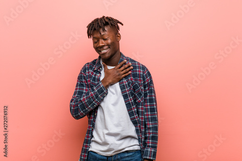 Fotografie, Obraz  Young african black man laughs out loudly keeping hand on chest.
