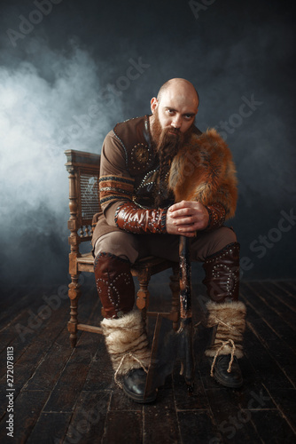 Bearded viking with axe sitting on chair Canvas Print