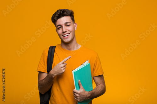 Fotografia Young student man holding books pointing with finger at you as if inviting come closer