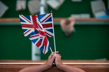 A Lady Holds Two Union Jack Flags As She Leans On A Handrail. Viewed From Above With Cruise Ship Outside Balconies Blurred Below