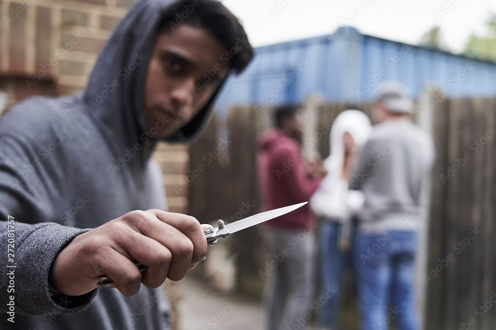 Fototapeta  Teenage Boy In Urban Gang Pointing Knife Towards Camera