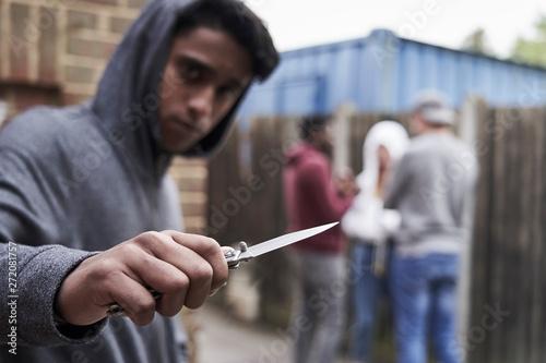 Foto  Teenage Boy In Urban Gang Pointing Knife Towards Camera