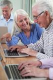 Tutor Helping Senior Man In Computer Class