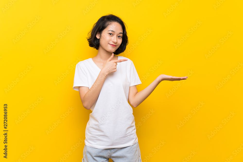 Fototapety, obrazy: Asian young woman over isolated yellow wall holding copyspace imaginary on the palm to insert an ad