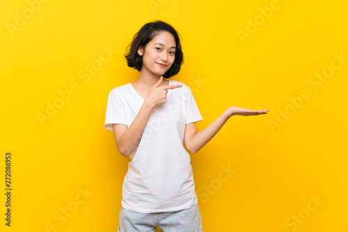 Fotografía  Asian young woman over isolated yellow wall holding copyspace imaginary on the p