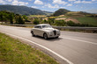 Classic car driving on winding road with nature in background