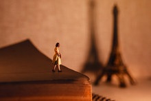 Dream Destination For Vacation. Travel In Paris, France. A Miniature Tourist Woman Standingon The Aged Book And Looking At The Eiffel Tower. Vintage Style